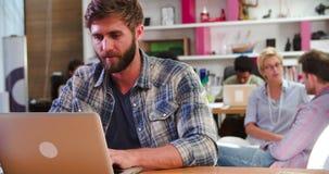 Επιχειρηματίας που εργάζεται στο lap-top στο πολυάσχολο γραφείο απόθεμα βίντεο