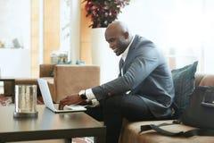 Επιχειρηματίας που εργάζεται στο lap-top στο λόμπι ξενοδοχείων Στοκ φωτογραφία με δικαίωμα ελεύθερης χρήσης