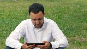Επιχειρηματίας που εργάζεται υπαίθρια με το ψηφιακό PC ταμπλετών στο πάρκο Χαλάρωση με μια ψηφιακή ταμπλέτα υπαίθρια φιλμ μικρού μήκους