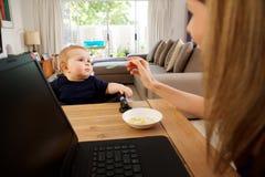 Επιχειρηματίας που εργάζονται στο σπίτι και ταΐζοντας μωρό Στοκ εικόνες με δικαίωμα ελεύθερης χρήσης