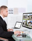 Επιχειρηματίας που ελέγχει ένα χαρτοφυλάκιο ιδιοκτησίας on-line Στοκ εικόνες με δικαίωμα ελεύθερης χρήσης