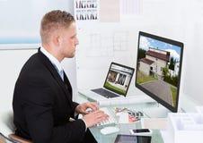 Επιχειρηματίας που ελέγχει ένα χαρτοφυλάκιο ιδιοκτησίας on-line Στοκ Εικόνες