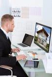 Επιχειρηματίας που ελέγχει ένα χαρτοφυλάκιο ιδιοκτησίας on-line Στοκ Εικόνα