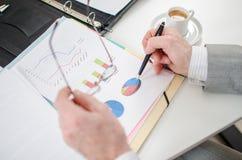 Επιχειρηματίας που ελέγχει τις οικονομικές γραφικές παραστάσεις Στοκ εικόνα με δικαίωμα ελεύθερης χρήσης