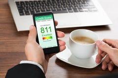 Επιχειρηματίας που ελέγχει το πιστωτικό αποτέλεσμα στο κινητό τηλέφωνο Στοκ φωτογραφία με δικαίωμα ελεύθερης χρήσης