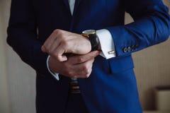Επιχειρηματίας που ελέγχει το χρόνο στο wristwatch του χέρι ατόμων ` s με ένα ρολόι Στοκ Φωτογραφία