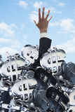 Επιχειρηματίας που θάβεται κάτω από μια μεγάλη ομάδα σημαδιών δολαρίων, που προσπαθεί να βγεί Στοκ Φωτογραφία