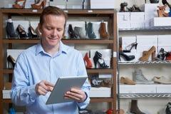 Επιχειρηματίας που διευθύνει μια σε απευθείας σύνδεση επιχείρηση παπουτσιών με την ψηφιακή ταμπλέτα Στοκ Φωτογραφία