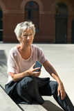 Επιχειρηματίας που κάνει ένα σπάσιμο και που κάθεται σε ένα σκαλοπάτι Στοκ Φωτογραφία