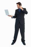 Επιχειρηματίας που κάνει ένα τηλεφώνημα χρησιμοποιώντας ένα lap-top Στοκ εικόνες με δικαίωμα ελεύθερης χρήσης