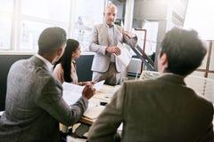 Επιχειρηματίας που κάνει μια παρουσίαση στους συναδέλφους στη αίθουσα συνδιαλέξεων Στοκ Εικόνα