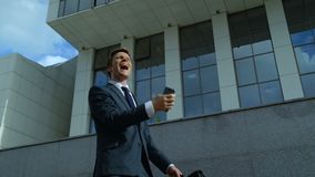Επιχειρηματίας που κάνει ναι τη χειρονομία, που χορεύει με την ευτυχία, καλές ειδήσεις από το τηλέφωνο απόθεμα βίντεο