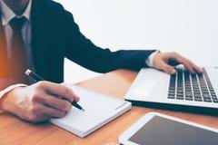 Επιχειρηματίας που κάνει τις σημειώσεις για χαρτί στην άκρη παραθύρων Στοκ Φωτογραφίες