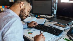 Επιχειρηματίας που κάνει τις σημειώσεις στο γραφείο γραφείων του Στοκ Εικόνες