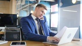 επιχειρηματίας που κάνει το πολλαπλό καθήκον, που λειτουργεί με τα έγγραφα, το lap-top και το τηλέφωνο Στοκ εικόνα με δικαίωμα ελεύθερης χρήσης