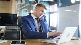 επιχειρηματίας που κάνει το πολλαπλό καθήκον, που λειτουργεί με τα έγγραφα, το lap-top και το τηλέφωνο απόθεμα βίντεο