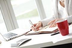 Επιχειρηματίας που καθιστά τις σημειώσεις στην αρχή. Στοκ φωτογραφία με δικαίωμα ελεύθερης χρήσης