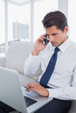 Επιχειρηματίας που καλεί με το τηλέφωνο κυττάρων του και που χρησιμοποιεί το lap-top του Στοκ φωτογραφία με δικαίωμα ελεύθερης χρήσης