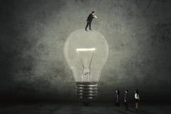 Επιχειρηματίας που καλεί τους συνεργάτες του από το lightbulb Στοκ Εικόνες
