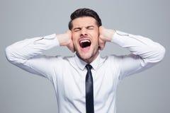 Επιχειρηματίας που καλύπτει τα αυτιά και την κραυγή του Στοκ Εικόνα