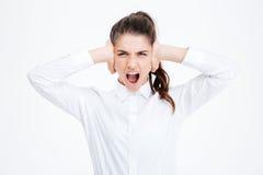 Επιχειρηματίας που καλύπτει τα αυτιά της και που φωνάζει πέρα από το άσπρο υπόβαθρο Στοκ Φωτογραφίες