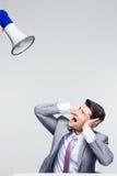 Επιχειρηματίας που καλύπτει τα αυτιά του από megaphone Στοκ Φωτογραφία