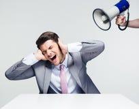 Επιχειρηματίας που καλύπτει τα αυτιά του από megaphone Στοκ φωτογραφία με δικαίωμα ελεύθερης χρήσης