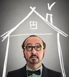 Επιχειρηματίας που κοιτάζει επάνω στη στέγη σπιτιών επάνω από το κεφάλι στοκ εικόνα με δικαίωμα ελεύθερης χρήσης