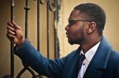Επιχειρηματίας που κοιτάζει επίμονα μέσω ενός φράκτη Στοκ Εικόνες