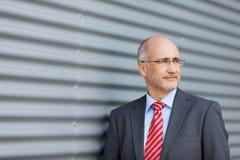 Επιχειρηματίας που κοιτάζει μακριά από το παραθυρόφυλλο Στοκ Φωτογραφίες