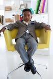 Επιχειρηματίας που κοιτάζει μακριά καθμένος στην πολυθρόνα Στοκ φωτογραφία με δικαίωμα ελεύθερης χρήσης