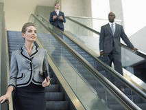 Επιχειρηματίας που κοιτάζει μακριά κινούμενη κάτω στην κυλιόμενη σκάλα Στοκ εικόνα με δικαίωμα ελεύθερης χρήσης