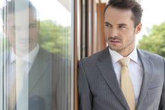Επιχειρηματίας που κοιτάζει μακριά κλίνοντας στην πόρτα γυαλιού Στοκ φωτογραφία με δικαίωμα ελεύθερης χρήσης