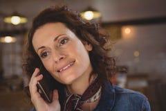 Επιχειρηματίας που κοιτάζει μακριά μιλώντας στο τηλέφωνο Στοκ Φωτογραφία