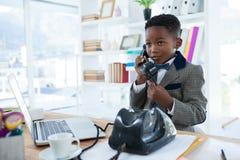 Επιχειρηματίας που κοιτάζει μακριά μιλώντας στο τηλέφωνο Στοκ Εικόνες