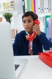 Επιχειρηματίας που κοιτάζει μακριά χρησιμοποιώντας το τηλέφωνο γραμμών εδάφους Στοκ Φωτογραφίες