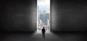 Επιχειρηματίας που κοιτάζει σε μια εικονική παράσταση πόλης από ένα σκοτεινό κενό δωμάτιο στοκ φωτογραφία