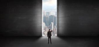 Επιχειρηματίας που κοιτάζει σε μια εικονική παράσταση πόλης από ένα σκοτεινό κενό δωμάτιο στοκ εικόνες