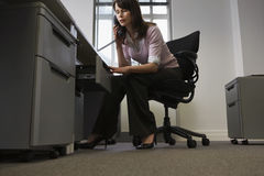 Επιχειρηματίας που κοιτάζει στο συρτάρι μιλώντας στο τηλέφωνο στην αρχή Στοκ φωτογραφία με δικαίωμα ελεύθερης χρήσης