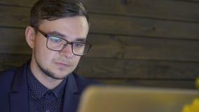 Επιχειρηματίας που κοιτάζει στο lap-top και που συζητά στον καφέ απόθεμα βίντεο