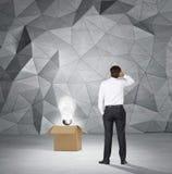 Επιχειρηματίας που κοιτάζει στο lightbulb στο κιβώτιο Στοκ φωτογραφία με δικαίωμα ελεύθερης χρήσης