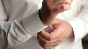 Επιχειρηματίας που κουμπώνει τα κουμπιά στα μανίκια πουκάμισων, κινηματογράφηση σε πρώτο πλάνο φιλμ μικρού μήκους