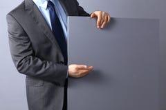Επιχειρηματίας που κρατά έναν κενό πίνακα, που δείχνει κάτι Στοκ φωτογραφία με δικαίωμα ελεύθερης χρήσης