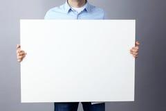 Επιχειρηματίας που κρατά έναν κενό πίνακα στο γκρίζο υπόβαθρο Στοκ εικόνα με δικαίωμα ελεύθερης χρήσης