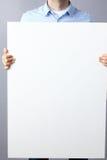 Επιχειρηματίας που κρατά έναν κενό πίνακα στο γκρίζο υπόβαθρο Στοκ εικόνες με δικαίωμα ελεύθερης χρήσης
