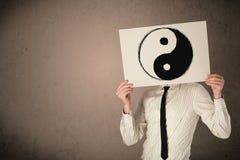 Επιχειρηματίας που κρατά ένα έγγραφο με ένα yin-yang σε το μπροστά από γεια Στοκ εικόνες με δικαίωμα ελεύθερης χρήσης