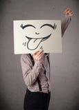 Επιχειρηματίας που κρατά ένα έγγραφο με το αστείο πρόσωπο smiley μπροστά από το χ Στοκ Φωτογραφία