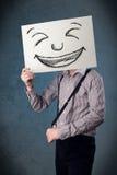 Επιχειρηματίας που κρατά ένα έγγραφο με το πρόσωπο smiley μπροστά από το hea του Στοκ Εικόνες