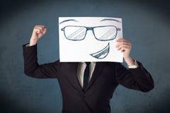 Επιχειρηματίας που κρατά ένα έγγραφο με το πρόσωπο smiley μπροστά από το hea του Στοκ εικόνα με δικαίωμα ελεύθερης χρήσης