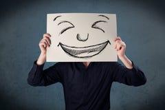 Επιχειρηματίας που κρατά ένα έγγραφο με το πρόσωπο smiley μπροστά από το hea του Στοκ φωτογραφία με δικαίωμα ελεύθερης χρήσης